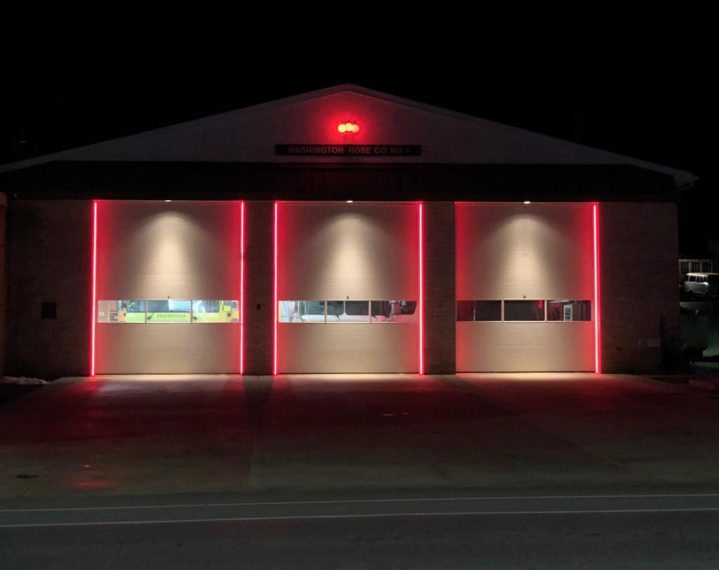 Red LEDs indicate the bay doors are closed.  Additionally, in line with history and tradition the red lights provide added identification of the firehouse. When the bay doors are closed a citizen in need can easily locate the firehouse to obtain help.